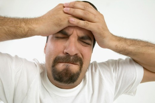Man with hands clasped across forehead : Stock Photo