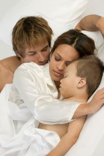 Close-up of mother and father sleeping with baby : Stock Photo
