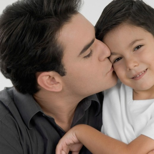 Close-up of a father kissing his son : Stock Photo