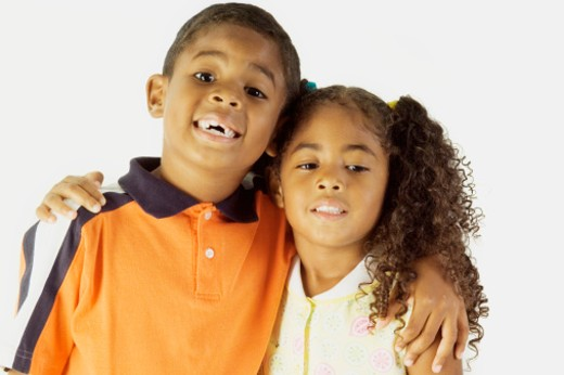 Close-up of a brother and his sister with their arm around : Stock Photo