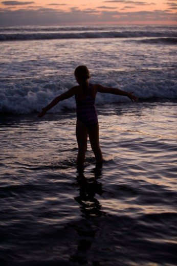 Rear view of a girl playing in the sea, San Diego, California, USA : Stock Photo