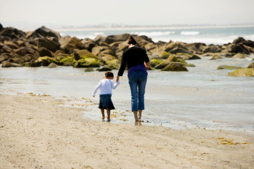 Rear view of a mother and her daughter walking on the beach, San Diego, California, USA : Stock Photo