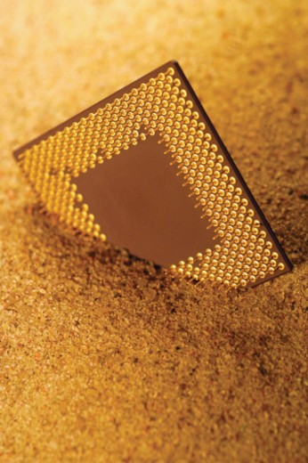 Stock Photo: 1598R-268679 Computer chip partially buried in sand