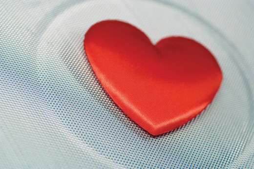 Red heart on silver screen, close-up : Stock Photo