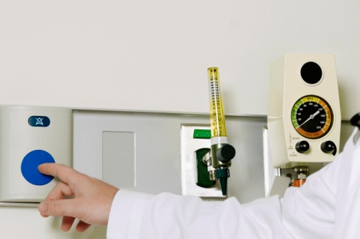Healthcare worker pushing button on wall : Stock Photo