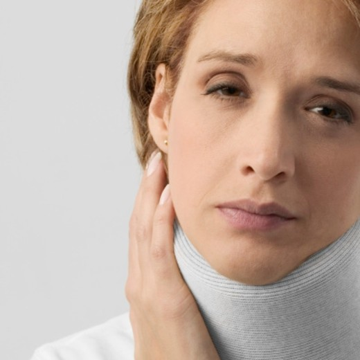 Mid adult woman in neck brace : Stock Photo