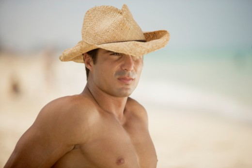 Close-up of a mid adult man wearing a straw hat : Stock Photo