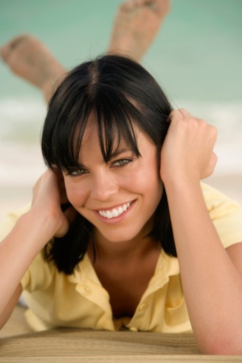 Stock Photo: 1598R-271091 Portrait of a young woman lying on the beach
