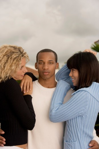 Low angle view of two young women and a young man : Stock Photo