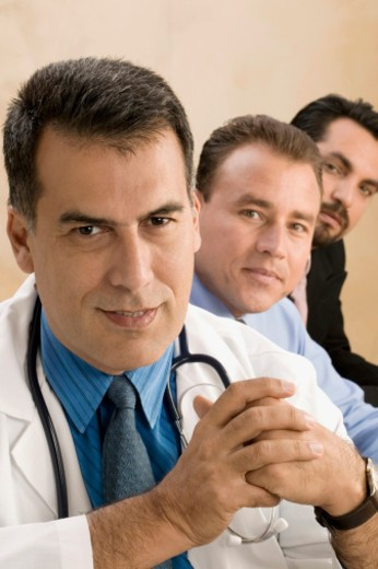 Stock Photo: 1598R-273193 Portrait of a doctor sitting with two businessmen