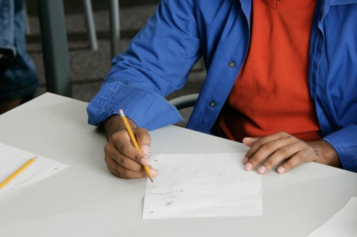 Mid section view of a young man writing on a paper : Stock Photo