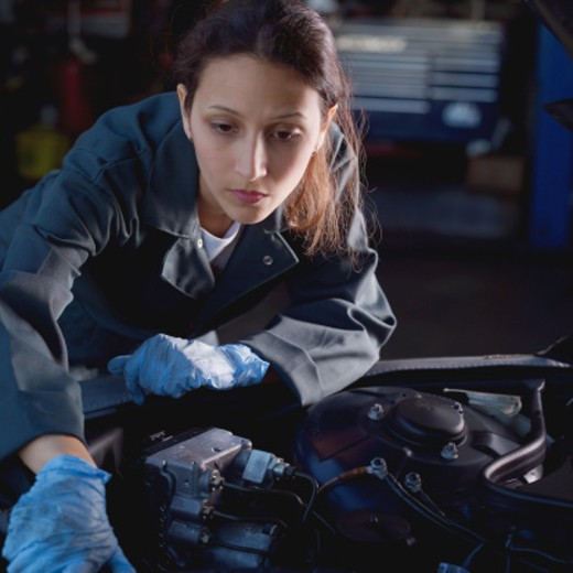 Stock Photo: 1598R-27387 Young female mechanic, leaning over car engine