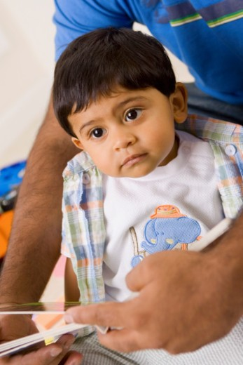 Close-up of a baby boy sitting on a person's lap : Stock Photo