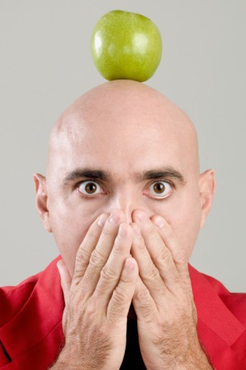Portrait of a mid adult man balancing a green apple on his head : Stock Photo