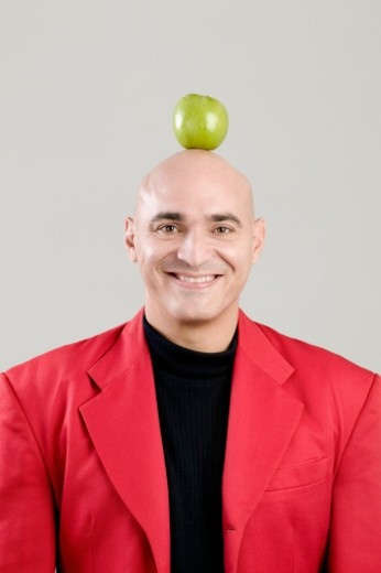 Stock Photo: 1598R-275383 Portrait of a mid adult man balancing a green apple on his head