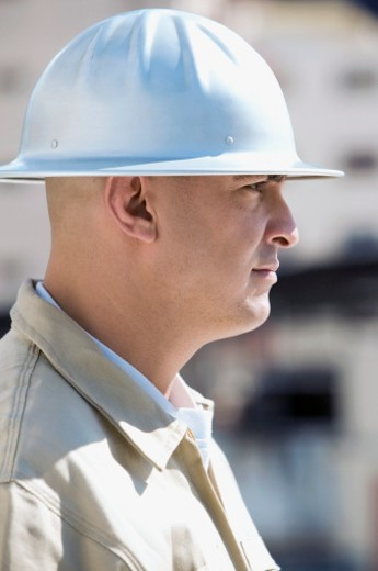 Side profile of a construction worker wearing a hard hat : Stock Photo