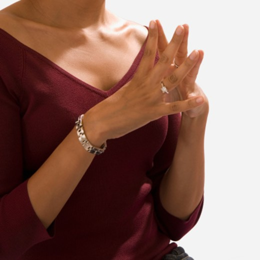 Mid section view of a woman with her hands clasped : Stock Photo