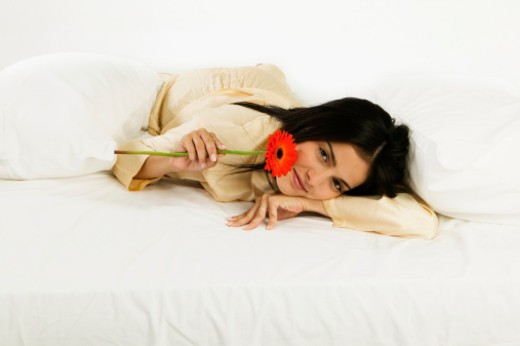 Portrait of a young woman lying on a bed : Stock Photo