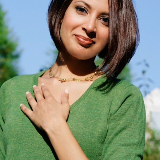 Portrait of a young woman with her hand on her chest : Stock Photo