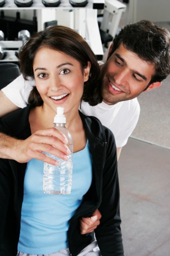 Portrait of a young couple smiling in a gym : Stock Photo