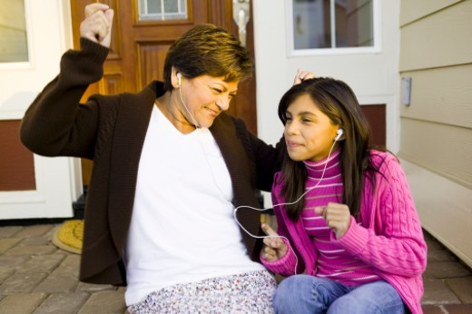 Grandmother and granddaughter (10-11) listening to music, dancing : Stock Photo