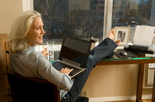 Mature woman with feet up, working on laptop : Stock Photo