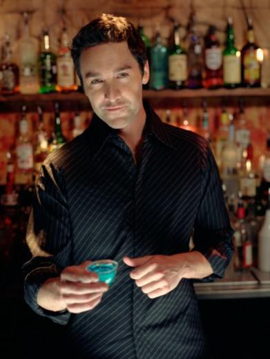 Bartender standing behind bar serving shot : Stock Photo