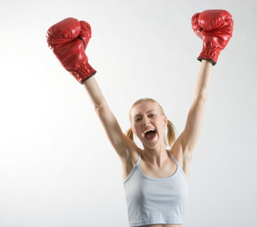 Stock Photo: 1598R-276972 Female boxer raising arms, smiling