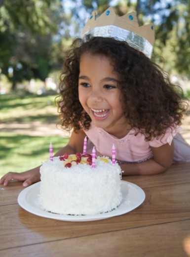 Girl (5-7) laughing by birthday cake : Stock Photo