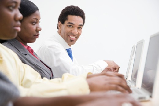 Business people using laptops, side view, upper half, differential focus : Stock Photo