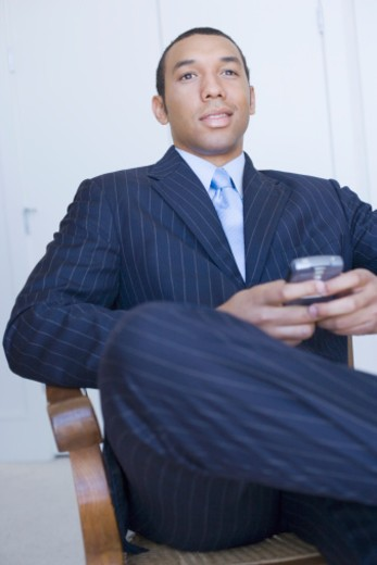 Stock Photo: 1598R-277574 Business man with palmtop, three quarter length