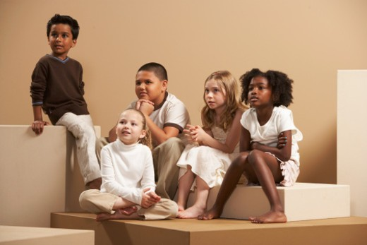 Boys and girls (5-7) sitting on large boxes : Stock Photo