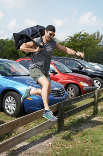 Stock Photo: 1598R-277832 Mature man carrying sports bag jumping over fence