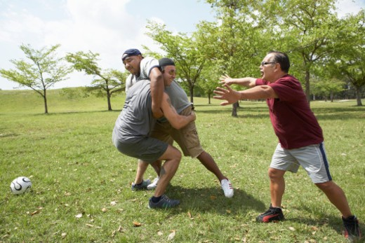 Stock Photo: 1598R-277846 Men wrestling playing soccer with referee