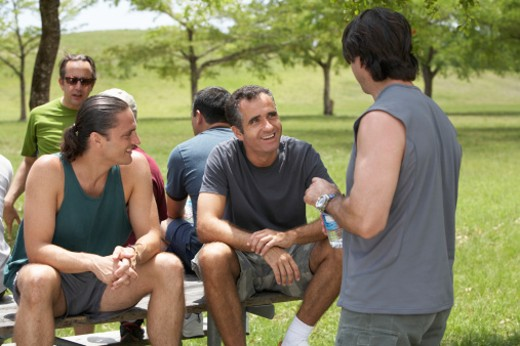 Group of men talking and resting on picnic table in park : Stock Photo