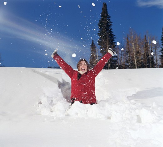 Young woman half-buried in snow, arms raised, smiling, portrait : Stock Photo