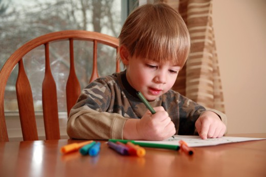 A cute 4 year old boy drawing a picture with markers at the dining room table. : Stock Photo