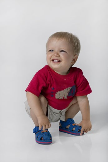 Boy (18-21 months) crouching in studio : Stock Photo