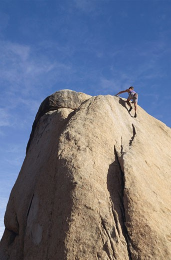 Rock climber at top of peak, rear view : Stock Photo