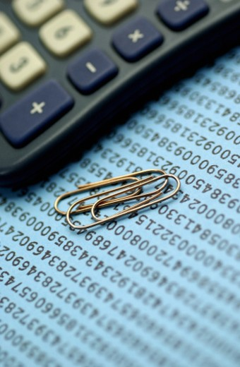 Close-up of paper clips near a calculator : Stock Photo