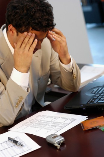 Businessman sitting at a desk with his hands on his head : Stock Photo