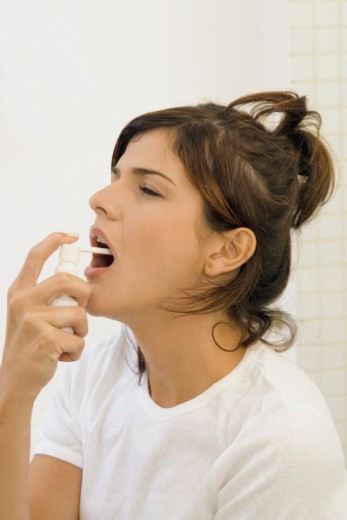 Young woman spraying mouth spray, close-up : Stock Photo