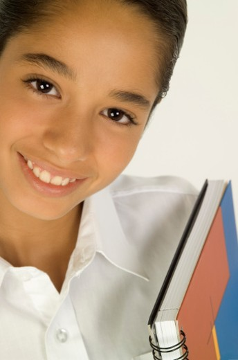 Stock Photo: 1598R-284593 Young girl carrying books and smiling, close-up
