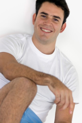 Man in casual clothes sitting against wall : Stock Photo