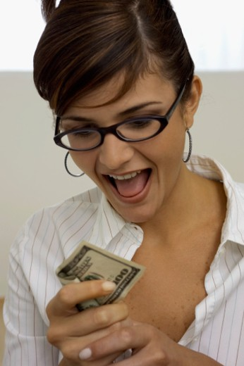 Portrait of excited young woman holding United States one hundred dollar bill, close-up : Stock Photo