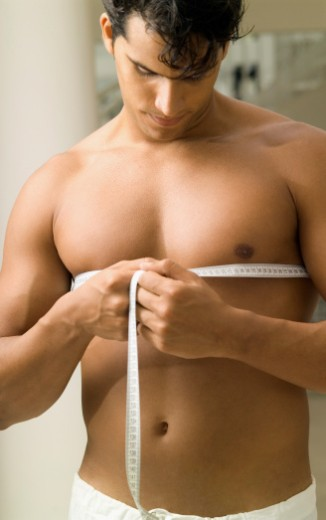 Young man measuring his chest with a measuring tape : Stock Photo