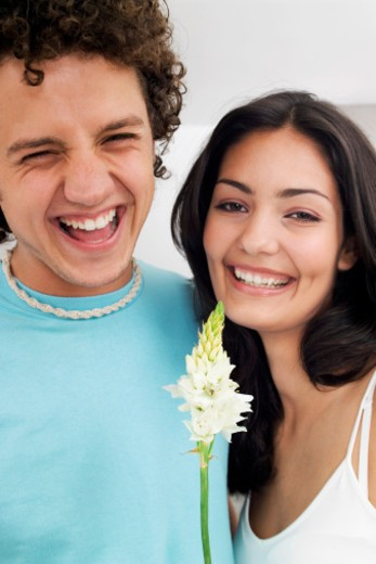 Stock Photo: 1598R-285102 Smiling young couple with flower indoors, close-up