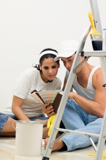 Stock Photo: 1598R-285415 Man and woman holding paint samples and sitting on floor with painting equipment around them