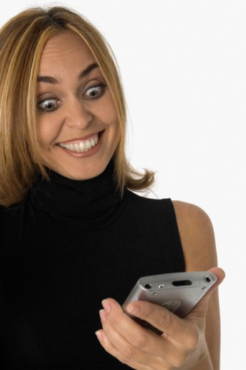 Surprised and smiling woman looking at hand held computer, close-up : Stock Photo