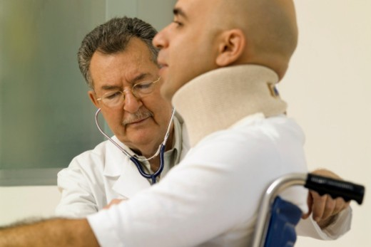 Male doctor examining a male patient in a wheel chair : Stock Photo